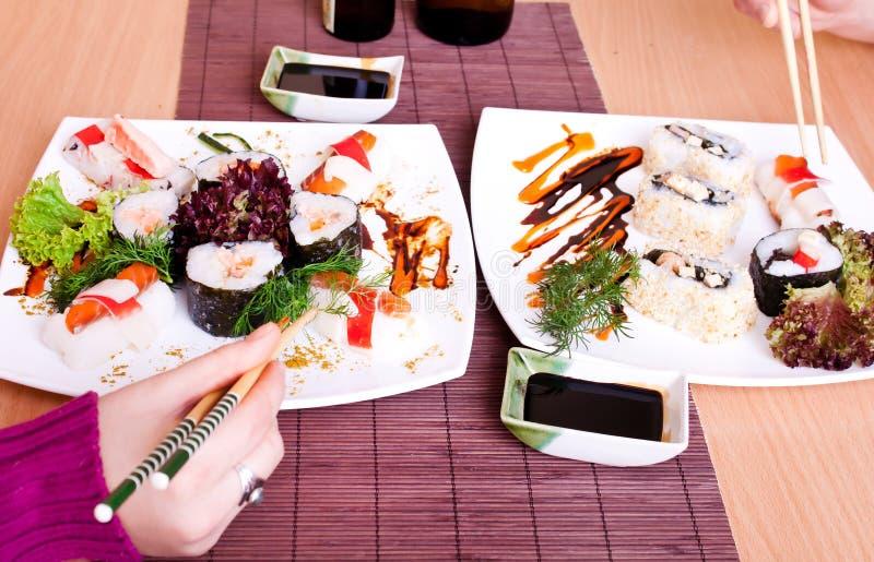 Eating sushi with chopsticks stock image