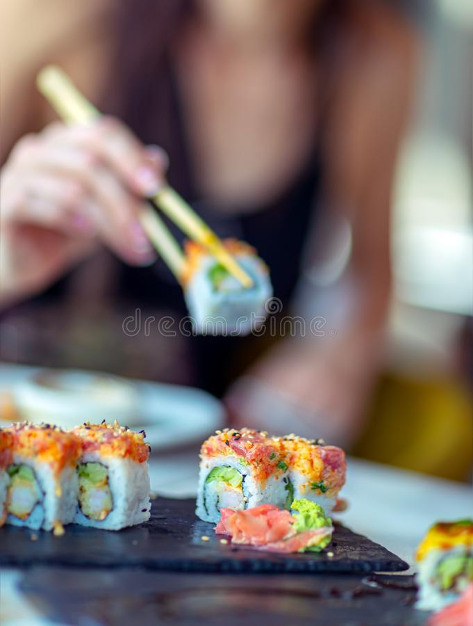 Eating sushi. In the restaurant, a woman using chopsticks takes a piece of roll, enjoying tasty and healthy food, traditional Asian cuisine stock photos