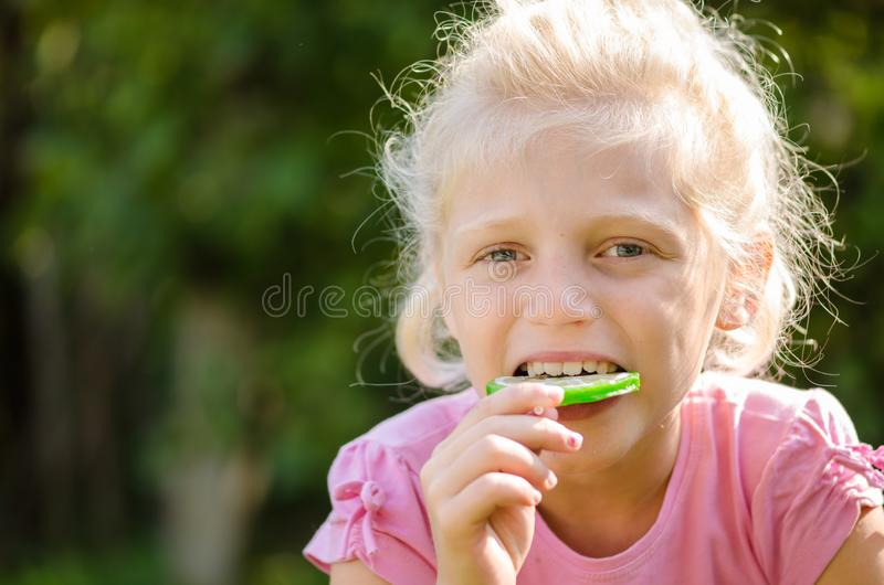 Eating sweet lollipop. Little girl holding a lollipop in hand royalty free stock photography