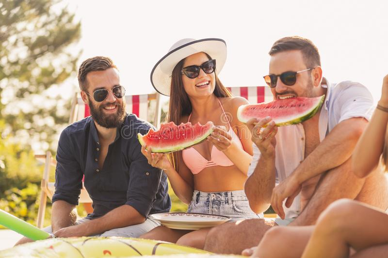 Eating watermelon at a poolside party. Group of friends at a poolside summer party, sitting at the edge of a swimming pool, eating cold watermelon slices and royalty free stock photo