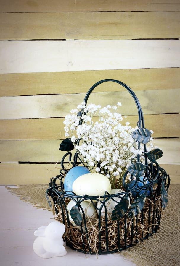 Eatser wizerunek zawiera zieleń, drucianego kosz z kolorowymi łaciastymi jajkami i dziecko oddech na nieociosanym drewnianym tle, fotografia stock