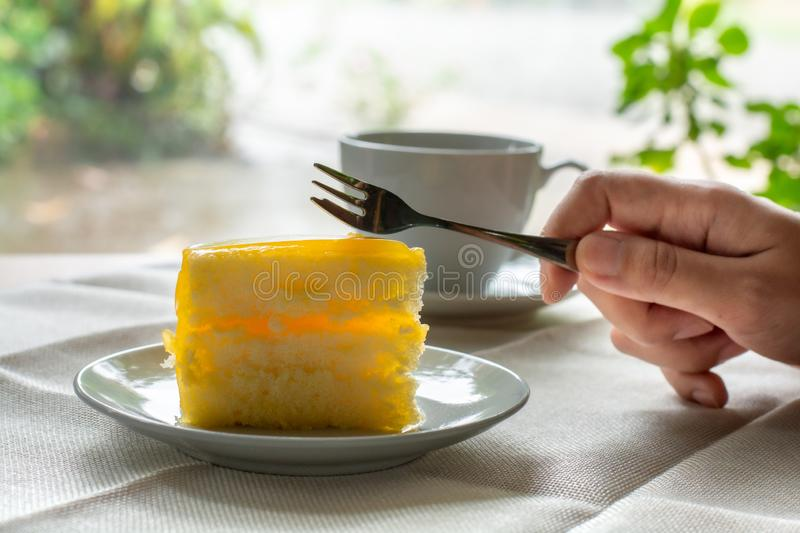 Eatting slice orange cake with metal fork served on white plate on table cloths in coffee times with green nature bokeh light. Background stock images
