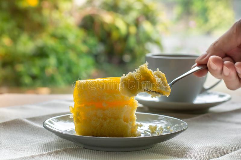 Eatting slice orange cake with metal fork served on white plate on table cloths in coffee times with green nature bokeh light. Background royalty free stock image