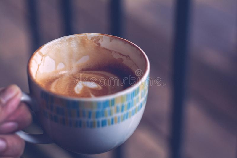 Eattng Hot coffee espresso, cappuccino, latte in ceramic white cup in hand with vintage tone, Copy space for your text royalty free stock photography