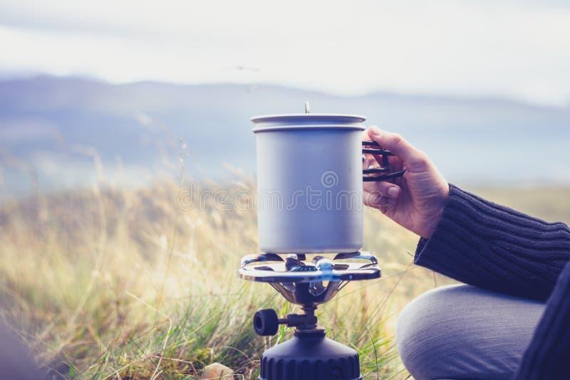 Eau bouillante de femme sur le fourneau de camping portatif image libre de droits