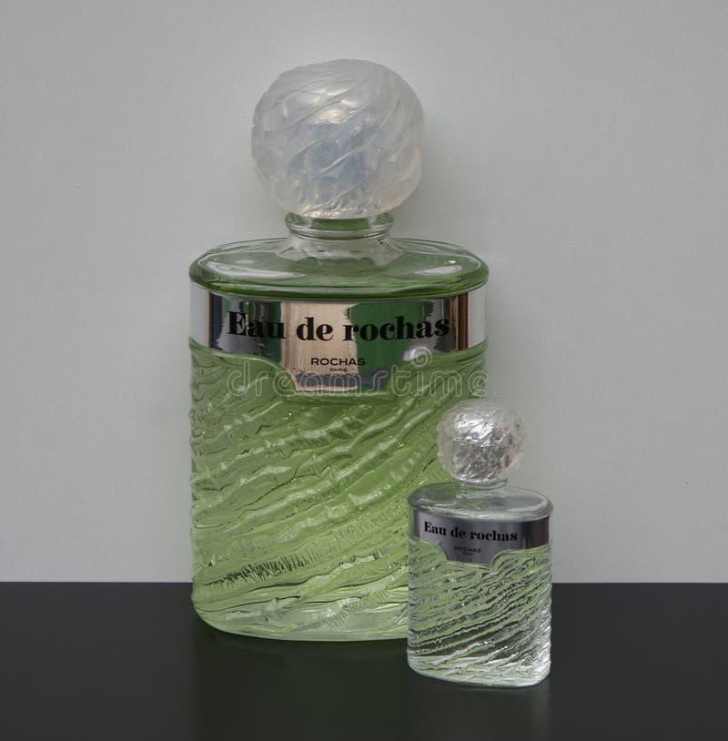 Eau de Rochas, fragrância para senhoras, grande garrafa de perfume ao lado de uma garrafa de perfume comercial foto de stock