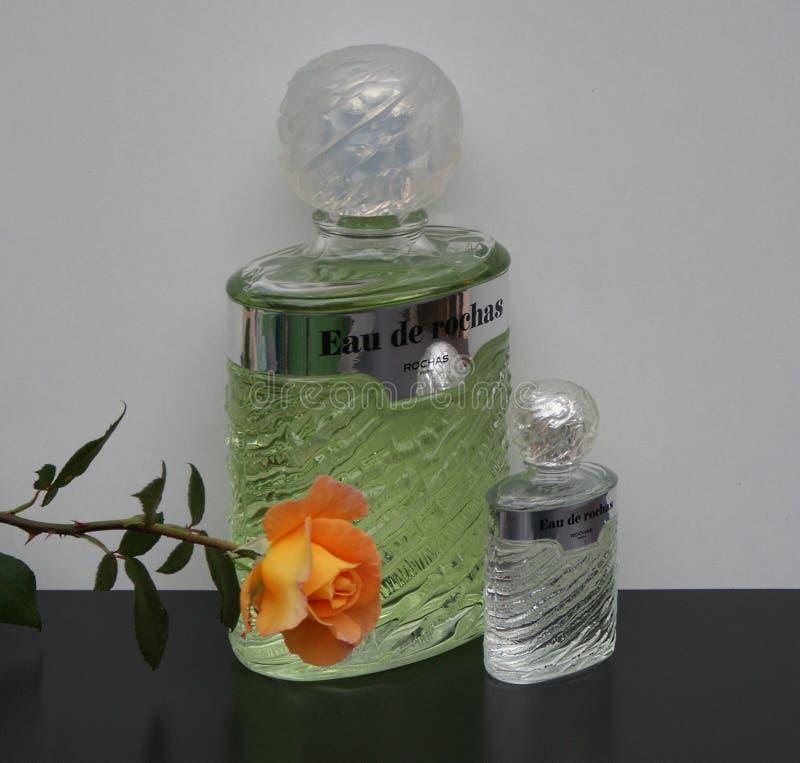 Eau de Rochas, fragrância para senhoras, grande garrafa de perfume ao lado de uma garrafa de perfume comercial decorada com um in imagem de stock royalty free