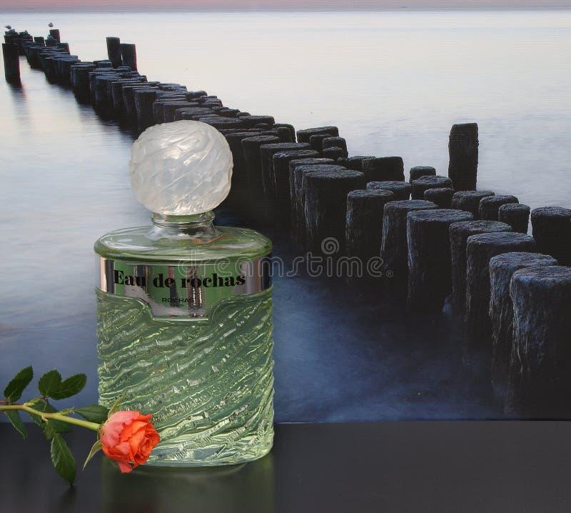 Eau de Rochas, fragrância para senhoras, grande garrafa de perfume na frente da imagem de um quebra-mar no mar decorado com uma r foto de stock