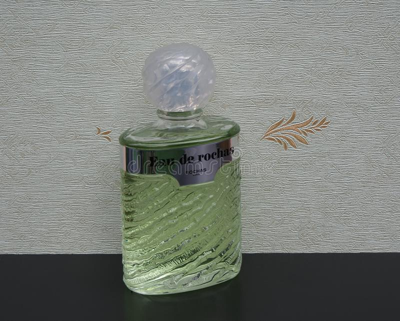 Eau de Rochas, fragrância para senhoras, grande garrafa de perfume na frente do wallcovering Elysee do cetim fotos de stock