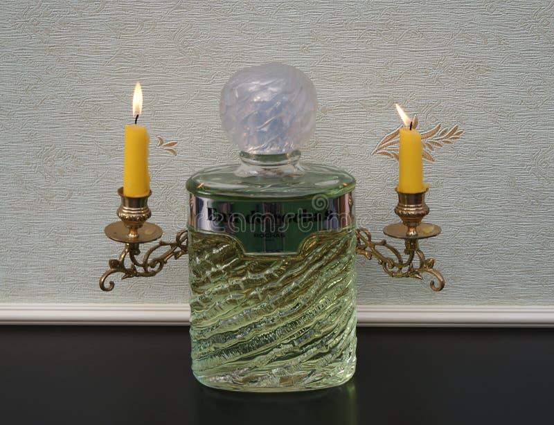 Eau de Rochas, fragrância para senhoras, grande garrafa de perfume na frente dos candelabros de um piano com velas de brilho foto de stock