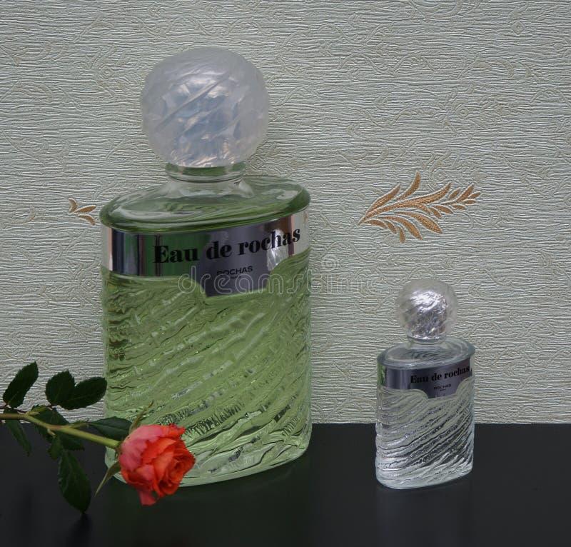 Eau de Rochas, fragranza per le signore, grande bottiglia di profumo accanto ad una bottiglia di profumo commerciale davanti al w fotografia stock libera da diritti