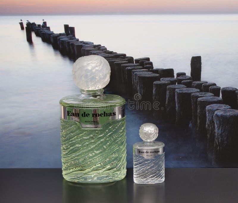 Eau de Rochas, fragranza per le signore, grande bottiglia di profumo accanto ad una bottiglia di profumo commerciale davanti all' fotografia stock libera da diritti