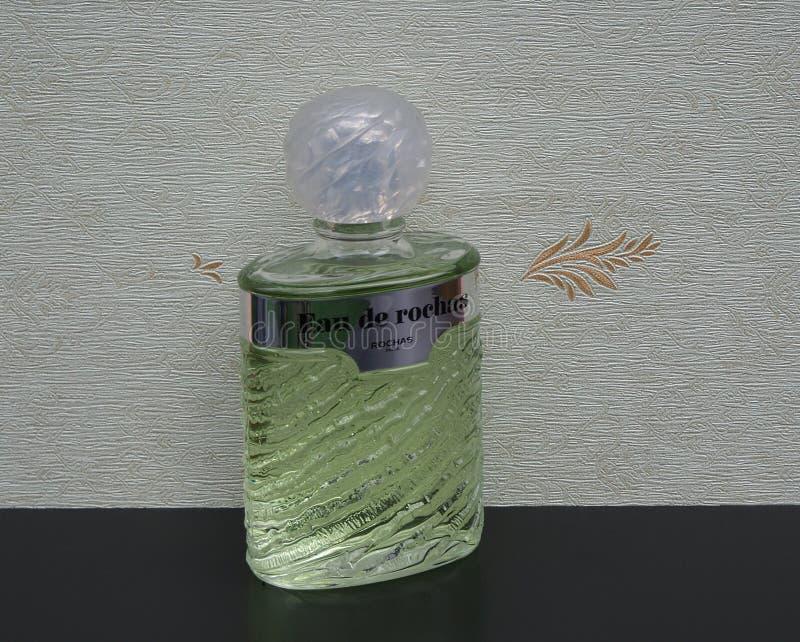 Eau de Rochas, fragranza per le signore, grande bottiglia di profumo davanti al wallcovering Elysee del raso fotografie stock