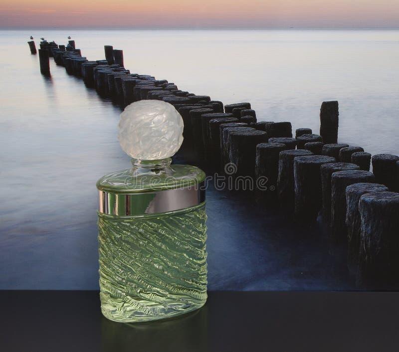 Eau de Rochas, fragranza per le signore, grande bottiglia di profumo davanti all'immagine di un frangiflutti nel mare immagine stock
