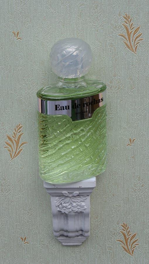 Eau de Rochas, fragranza per le signore, grande bottiglia di profumo su una console antica della parete con l'ornamento fotografie stock
