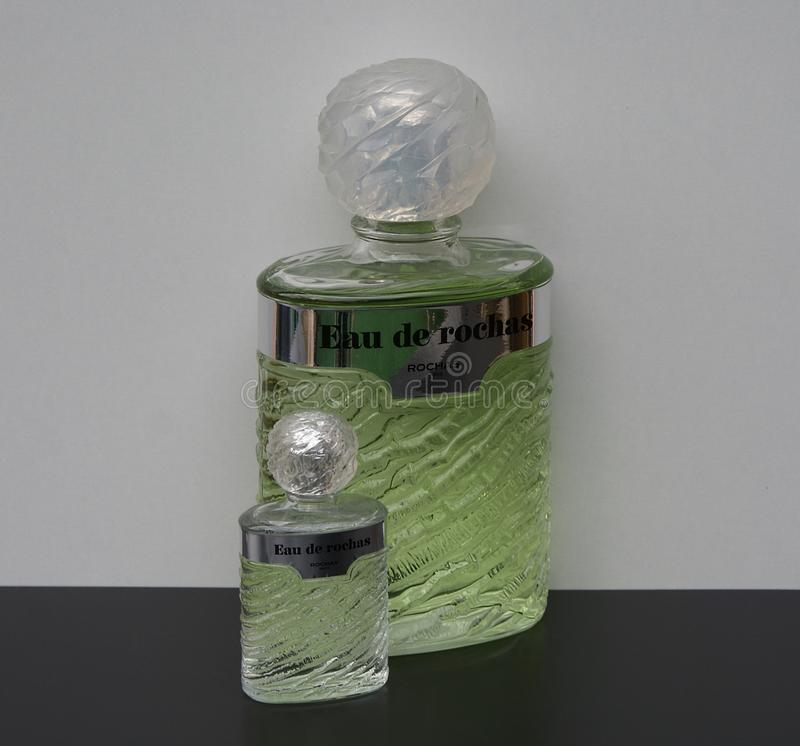 Eau DE Rochas, geur voor dames, grote parfumfles naast een commerciële parfumfles stock afbeeldingen