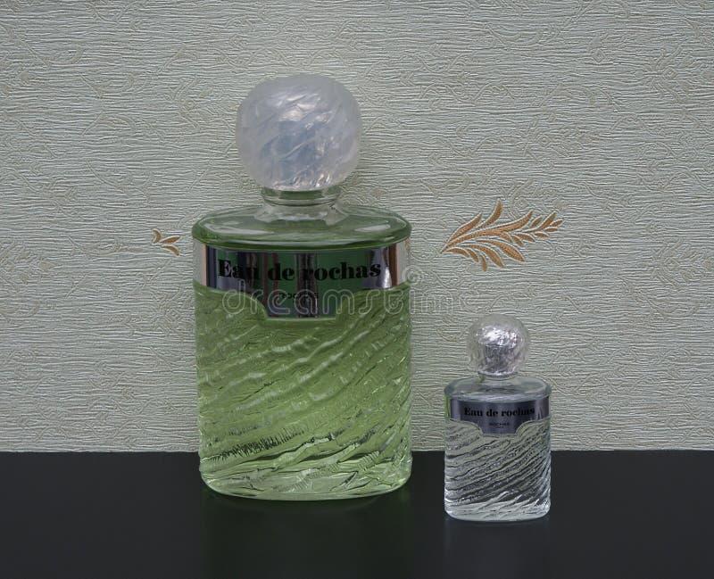 Eau DE Rochas, geur voor dames, grote parfumfles naast een commerciële parfumfles voor satijn het wallcovering stock foto