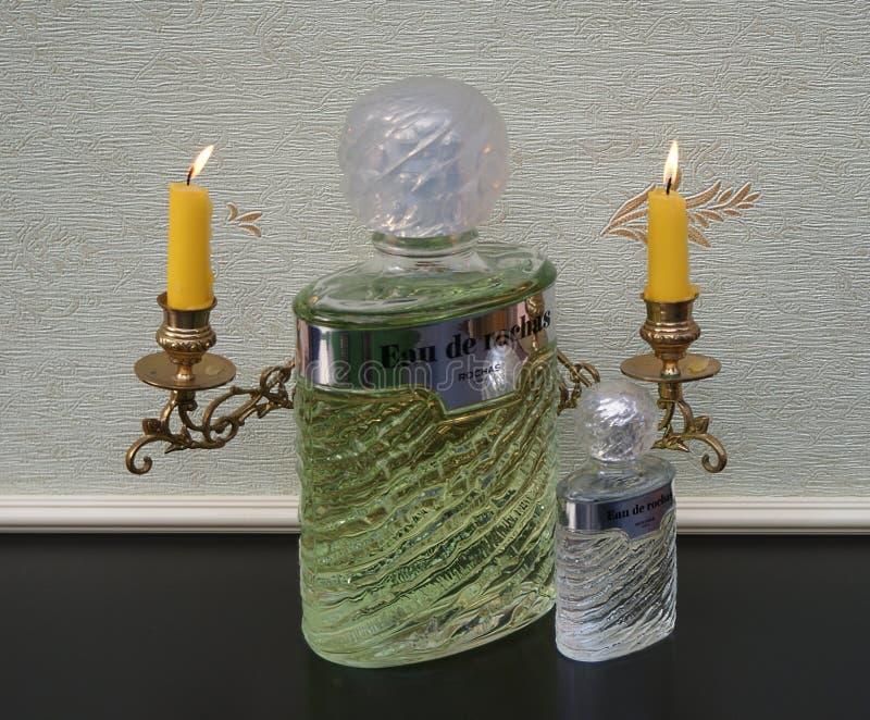 Eau DE Rochas grote parfumfles naast een commerciële parfumfles voor een pianokandelabers met glanzende kaarsen royalty-vrije stock afbeelding