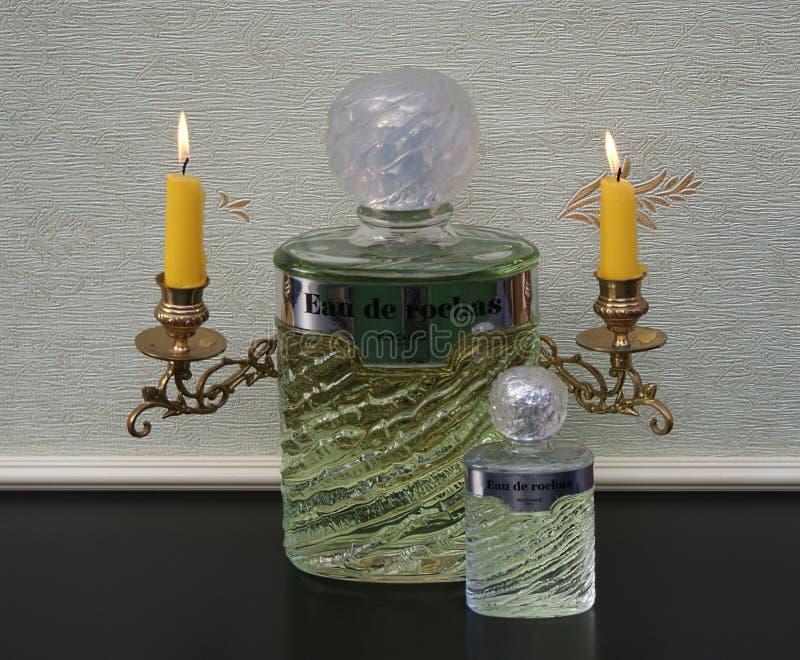 Eau DE Rochas, grote parfumfles naast een commerciële parfumfles voor een pianokandelabers met glanzende kaarsen stock foto's