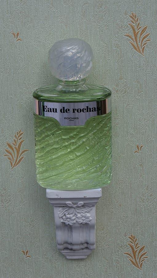 Eau De Rochas, woń dla dam, wielka pachnidło butelka na antyk ściany konsoli z ornamentem obraz royalty free