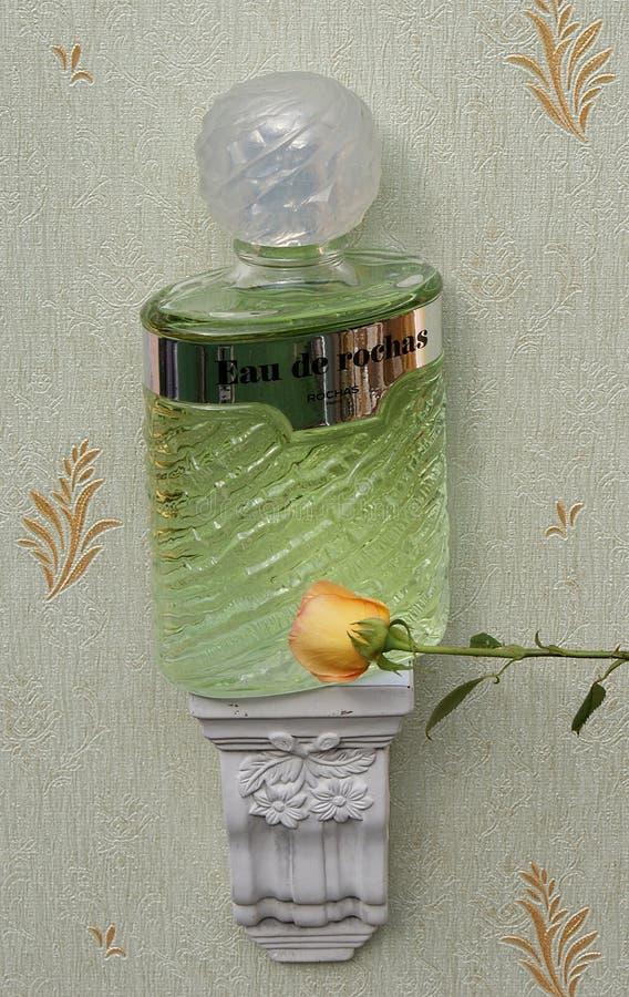 Eau De Rochas, woń dla dam, wielka pachnidło butelka na antyk ściany konsoli z ornamentem dekorującym z angielszczyzny wzrastał obrazy royalty free