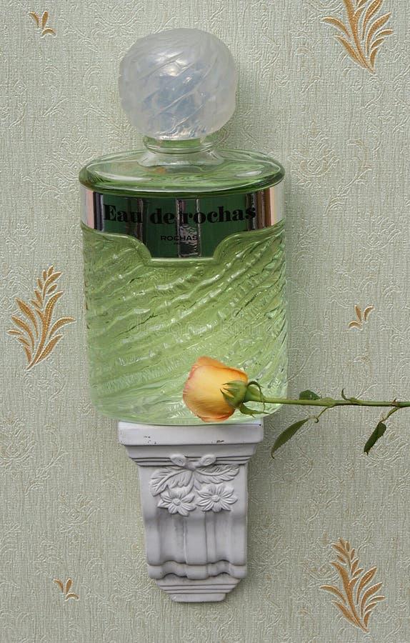 Eau De Rochas, woń dla dam, wielka pachnidło butelka na antyk ściany konsoli z ornamentem dekorującym z angielszczyzny wzrastał obrazy stock