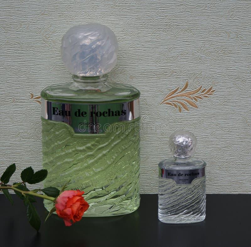 Eau De Rochas, woń dla dam, wielka pachnidło butelka obok handlowej pachnidło butelki przed atłasowym wallcovering zdjęcia royalty free