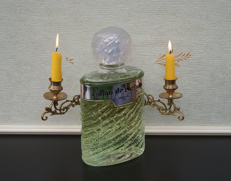 Eau De Rochas, woń dla dam, wielka pachnidło butelka przed fortepianowi kandelabry z olśniewającymi świeczkami zdjęcia stock