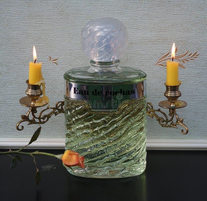 Eau De Rochas, woń dla dam, wielka pachnidło butelka przed kandelabry z olśniewającymi świeczkami dekorował z różą obrazy stock