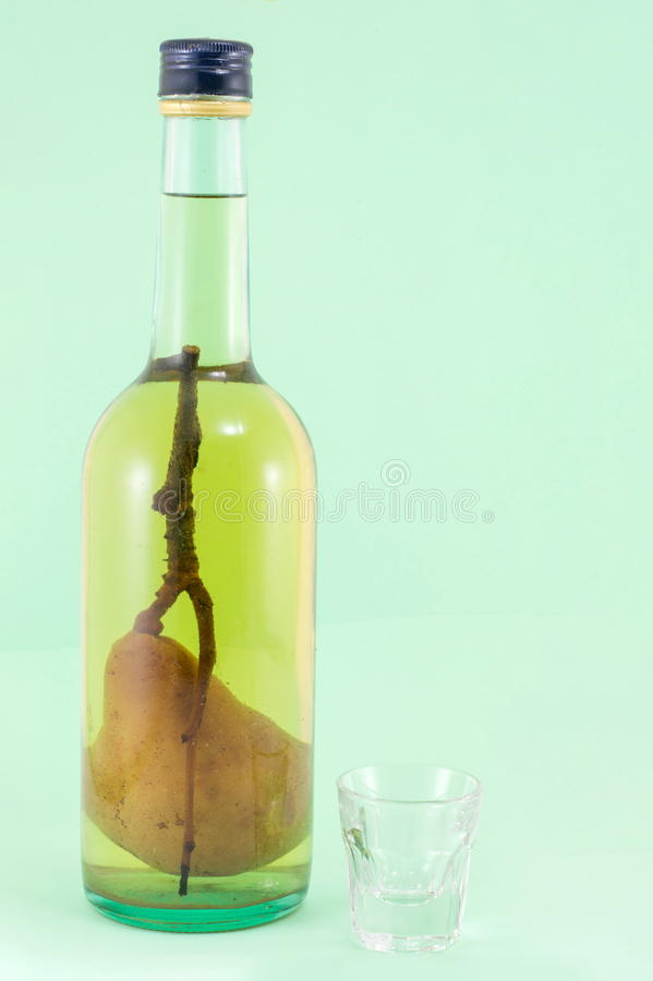 Eau-de-vie fine de poire avec la poire dans la bouteille photo stock