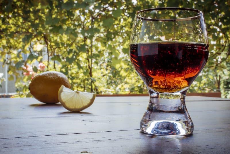 Eau-de-vie fine ou cognac dans le verre avec le citron sur la table Table en bois et texture verte de fond de raisin photo stock