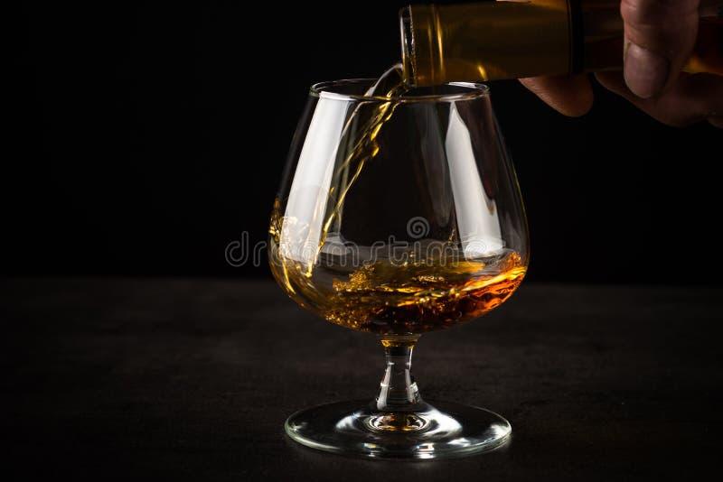 Eau-de-vie fine ou cognac se renversante dans le verre photo libre de droits