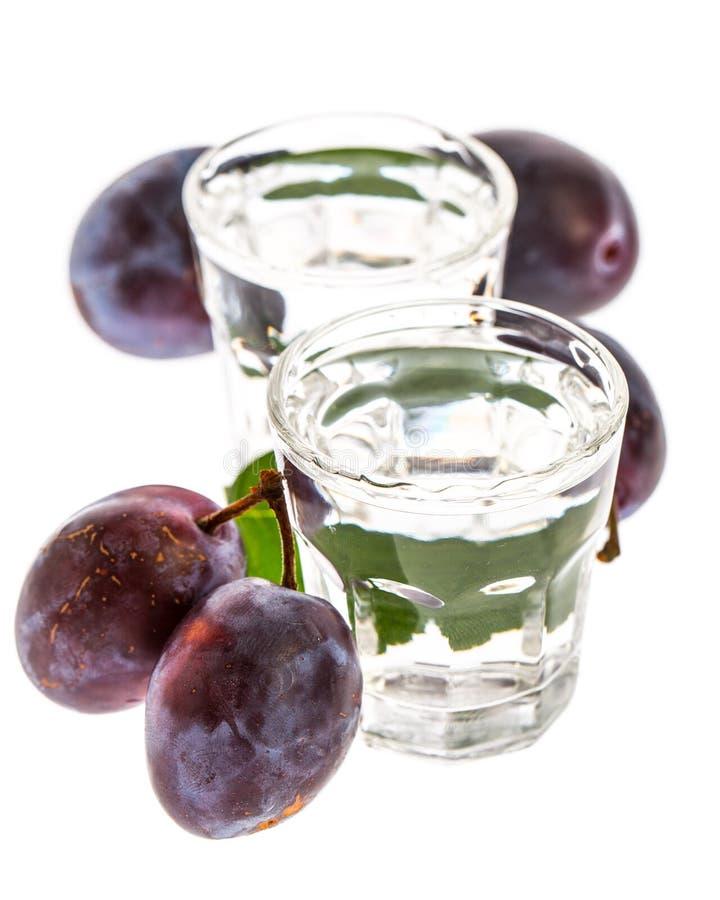 Eau-de-vie fine de prune avec des prunes d'isolement sur le fond blanc photographie stock