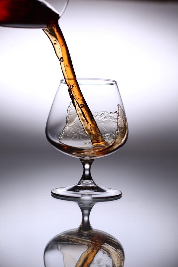 Eau-de-vie fine se renversante dans un verre photo stock