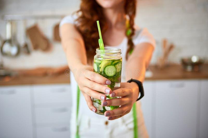 Eau douce potable de jeune femme avec le concombre, le citron et les feuilles de la menthe du verre dans la cuisine Mode de vie e photos libres de droits