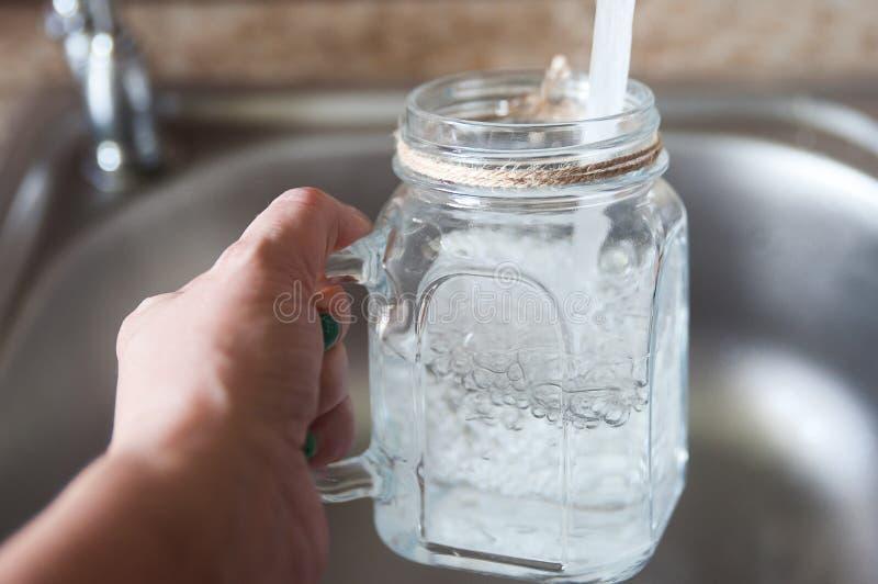Eau du robinet dans un verre image stock