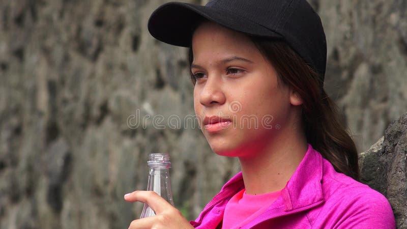 Eau en bouteille potable de fille assoiffée photographie stock libre de droits