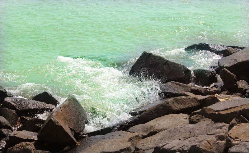 Eau et vagues de mer sur les roches avec l'éclaboussure dans la plage photos libres de droits