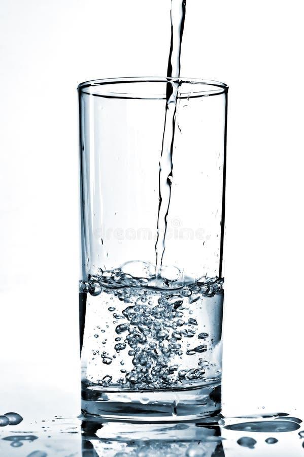 arrosez l'versement dans un verre images stock