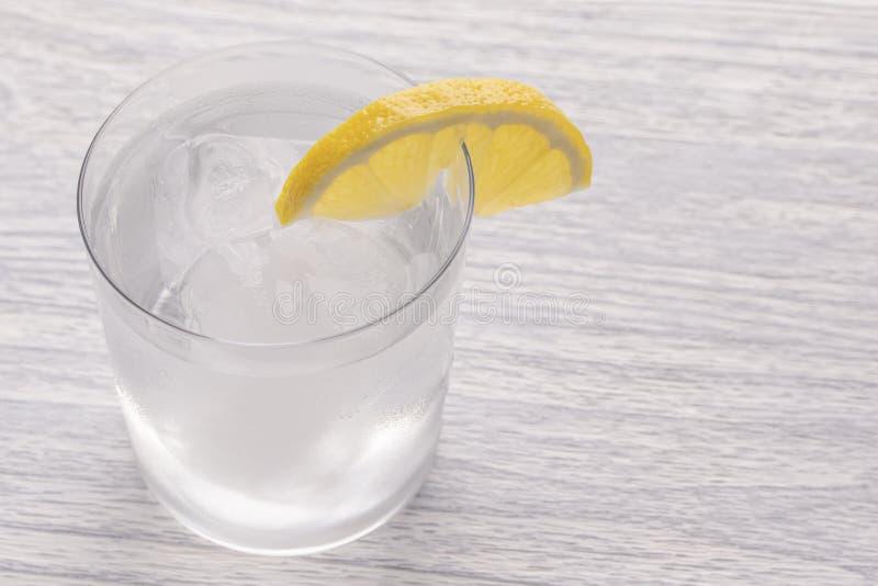 Eau froide régénératrice avec le citron Avec de la glace tout préparé Est après un couteau après coupure du fruit Verre de Misted image libre de droits