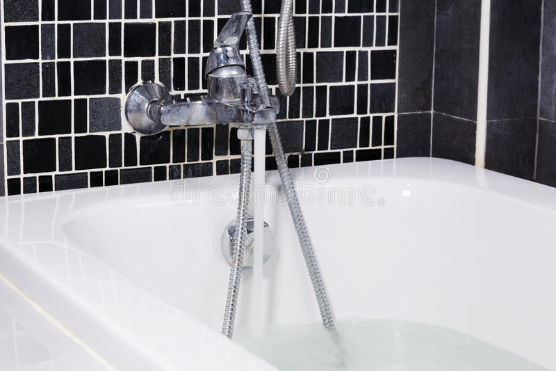 Eau libre de robinet dans la baignoire dans la salle de bains photos stock
