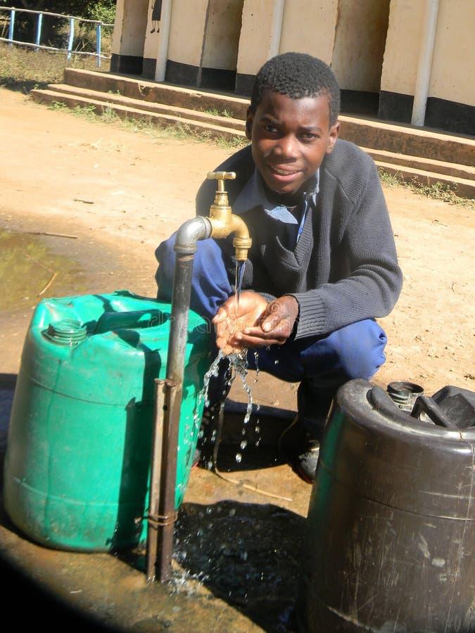 Eau potable d'enfant africain de robinet images libres de droits