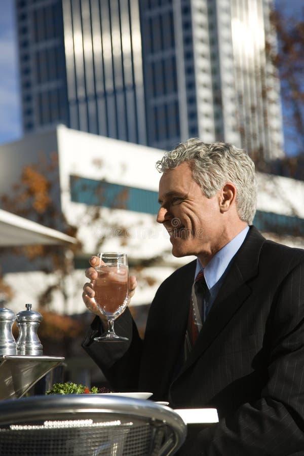 Eau potable d'homme d'affaires à la table. images stock