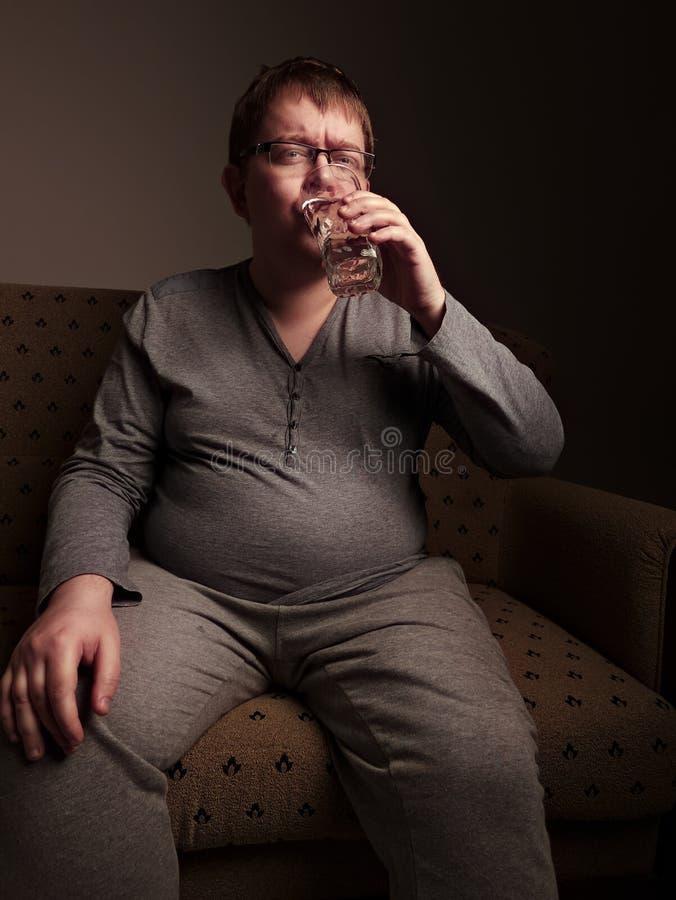 Eau potable d'homme de poids excessif image stock