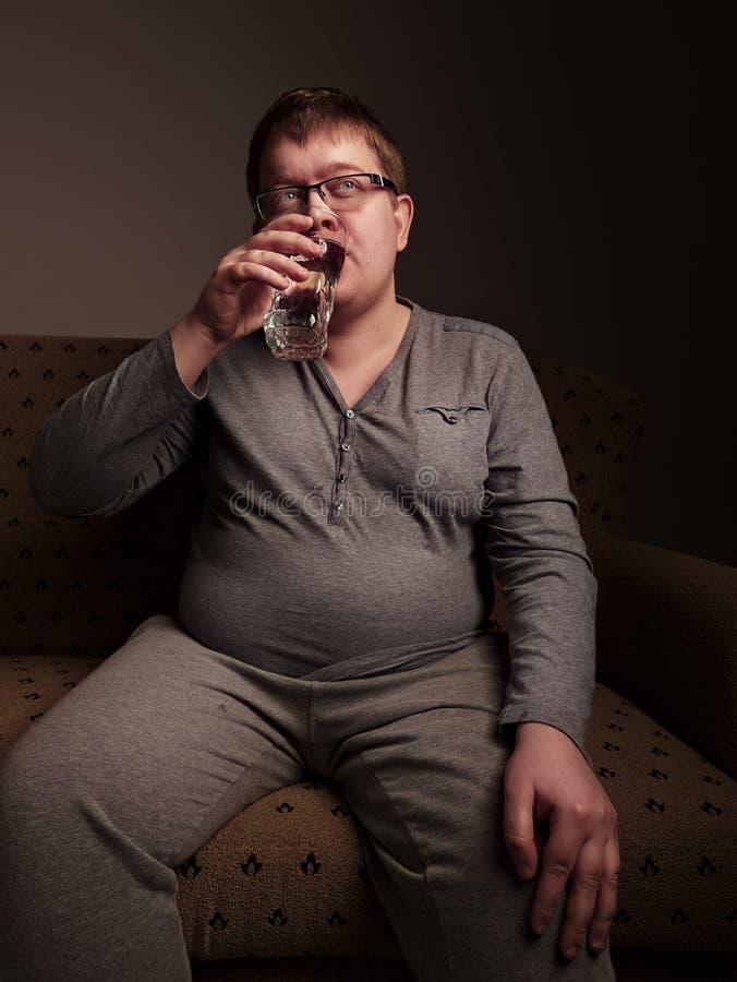 Eau potable d'homme de poids excessif photo stock