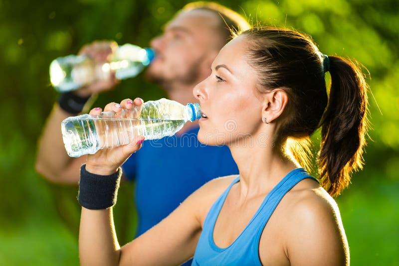 Eau potable d'homme et de femme de bouteille après exercice de sport de forme physique photo stock