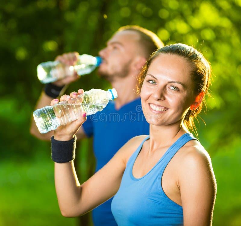 Eau potable d'homme et de femme de bouteille après exercice de sport de forme physique photo libre de droits