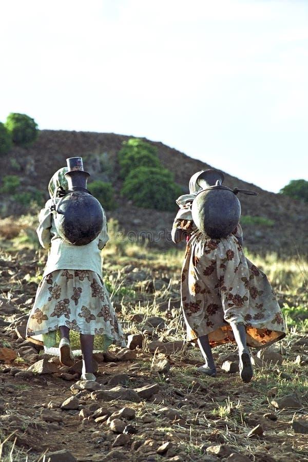 Eau potable de crochet éthiopien de femmes en montagnes images libres de droits