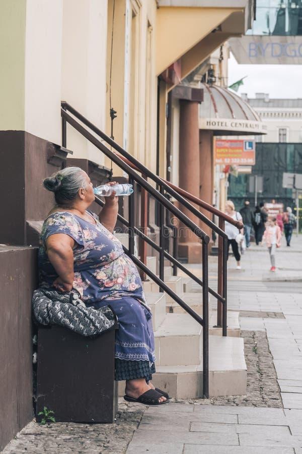 Eau potable de dame âgée photographie stock