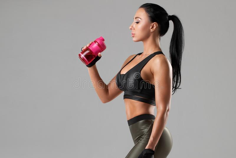 Eau potable de femme active d'une bouteille, La fille sportive éteint la soif images stock